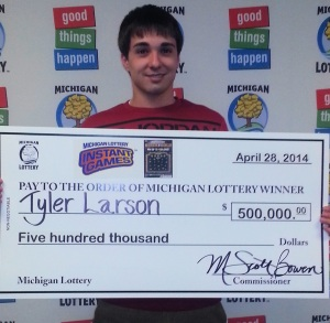 Tyler Larson, of Escanaba, holding his big check for winning a top prize in the Michigan Lottery's Black & Gold instant game. (Photo courtesy of the Michigan Lottery.)