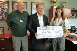 Diane Allen (right) poses for a photo with her father, Judson Ross (left) Michigan State University basketball coach Tom Izzo after accepting her Excellence in Education Award from the Michigan Lottery.