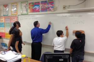 Joseph Lacey (center) works with students in his classroom at the Clippert Academy in Detroit.