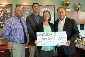 Audra Kowalski (second from right) poses for a photo with her husband, Ben Kowalski (second from left), principal, Tom Berriman (left) and Michigan State University basketball coach Tom Izzo after accepting her Excellence in Education Award from the Michigan Lottery.