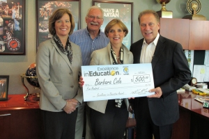 Barbara Cole (right) poses for a photo with her husband, Tom Cole (second from left), principal, Karen Friberg (left) and Michigan State University basketball coach Tom Izzo after accepting her Excellence in Education Award from the Michigan Lottery.