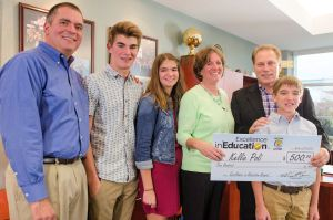 Kellie Poli (third from right) poses for a photo with (left to right) her husband, Matt, son, Nicholas, daughter, Allison, Michigan State University basketball coach Tom Izzo, and son Benjamin after accepting her Excellence in Education Award from the Michigan Lottery.