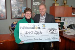 Kristin Higgins poses for a photo with Michigan State University basketball coach, Tom Izzo, after accepting her Excellence in Education Award from the Michigan Lottery.
