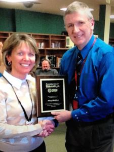 Mary Micklow accepts her Excellence in Education Award from Marquette Senior High School Principal, Bob Anthony.