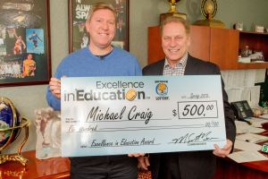 Michael Craig poses for a photo with Michigan State University basketball coach, Tom Izzo, after accepting his Excellence in Education Award from the Michigan Lottery.