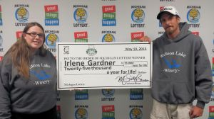 Irlene Gardner and her fiancee pose for a photo after collecting Gardner's first $25,000 payment.
