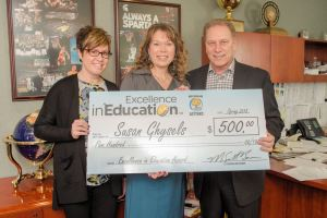 Susan Ghysels (center) poses for a photo with her colleague and friend, Jen Haberiling, and Michigan State University basketball coach, Tom Izzo, after accepting her Excellence in Education Award from the Michigan Lottery.