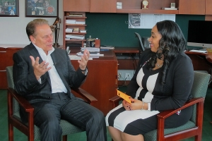 Angela Ensley talks with Michigan State University basketball coach, Tom Izzo, after accepting her Excellence in Education award.