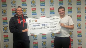 Michael Roberts (right) poses for a photo with his roommate after collecting his Fantasy 5 jackpot prize.