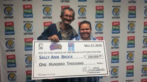 Sally Ann Brock and her husband, Dale, smile after claiming a $100,000 prize she won playing Bonus Ball Bingo.