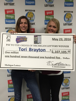 Tori Brayton and her girlfriend, Rebecca, pose for a photo after collecting Brayton's $1,000 a week for life prize.