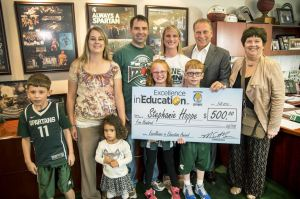 Stephanie Hoppe (center) poses for a photo with her husband, Douglas, mother-in-law, Jackie, sister-in-law, Sheila, children; Taylor, Zachary, and Michael, and niece, Carleigh after accepting her Excellence in Education award from Michigan State University basketball coach Tom Izzo.