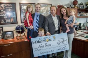 Adam Burns poses for a photo with his wife, Grace, and children, (from left to right) Isla, John, and Anna, after accepting his Excellence in Education award from Michigan State University basketball coach Tom Izzo.