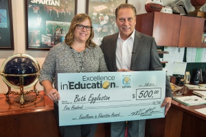 Beth Eggleston poses for a photo after accepting her Excellence in Education award from Michigan State University basketball coach Tom Izzo.