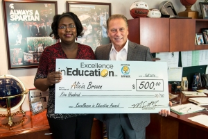 Alicia Brown poses for a photo after accepting her Excellence in Education award from Michigan State University basketball coach Tom Izzo.