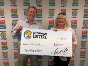 Lottery Commissioner, Aric Nesbitt, presents Debbie Gough with a check for her $60,923 Club Keno The Jack prize.