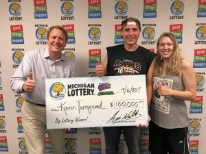 Lottery Commissioner, Aric Nesbitt, poses for a photo with Kainin Turnipseed and his girlfriend, Jessica, during their visit to Lottery headquarters.