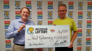 Michigan Lottery Commissioner, Aric Nesbitt, presents Paul Kuharevicz Mega Millions winner with a check for $1 million.