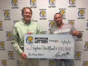 Michigan Lottery Commissioner, Aric Nesbitt, presents Stephen Strickland with a check for $100,000.