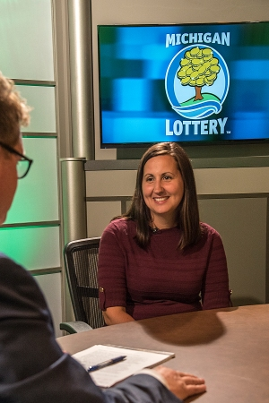 Jessica Moore is interviewed after being presented with an Excellence in Education award from the Michigan Lottery.