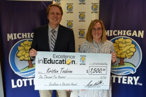 Kristen Toadvine poses for a photo with Michigan Lottery Commissioner, Aric Nesbitt, after accepting her Excellence in Education Award.