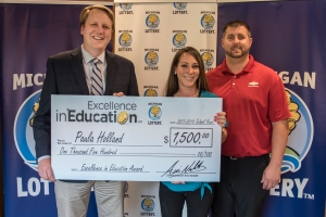Paula Holland poses for a photo with her husband, Derrick, and Michigan Lottery Commissioner, Aric Nesbitt, after accepting her Excellence in Education Award.