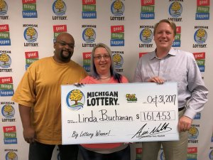 Michigan Lottery Commissioner, Aric Nesbitt, presents Linda and David Buchanan with a check for $161,453.