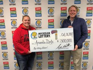 Amanda Dietz smiles after receiving a $300,000 check from Lottery Commissioner, Aric Nesbitt.
