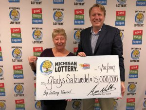 Gladys Salzwedel poses for a photo with Lottery Commissioner, Aric Nesbitt, after claiming her $5 million Mega Millions prize.