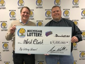 Lottery Commissioner, Aric Nesbitt, presents Mark Clark with a check for $4 million.