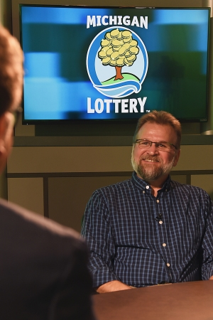Mark Eberhard is interviewed after being presented with an Excellence in Education award from the Michigan Lottery.