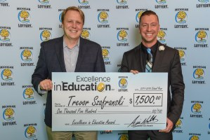 Trevor Szafranski poses for a photo with Michigan Lottery Commissioner, Aric Nesbitt, after accepting his Excellence in Education Award.