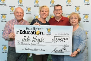 Julie Wright (center) poses for a photo with her step-father, Jim Rivard, husband, Lorin, and mother, Barb Rivard, after accepting her Excellence in Education Award.